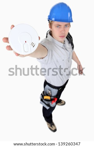Builder holding smoke alarm - stock photo