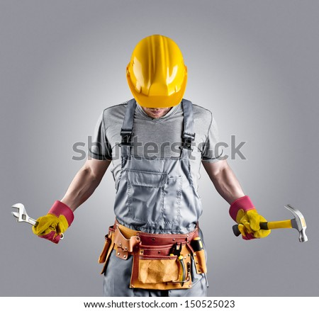 builder in a helmet with a hammer and a wrench - stock photo