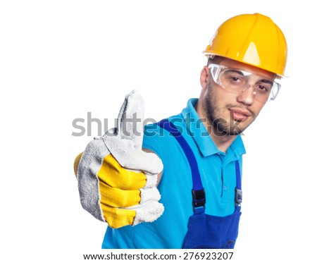 Builder in a protective hardhat and gloves showing thumbs up  gesture of approval and success. Focus on hand, isolated on white background - stock photo