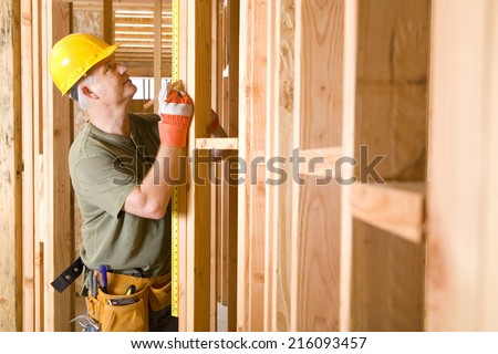 Builder in hardhat measuring beam, side view - stock photo