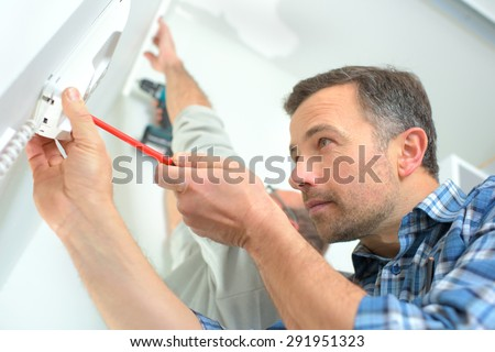 Builder installing an intercom - stock photo