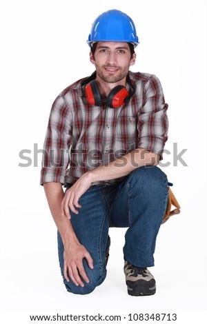 Builder kneeling - stock photo