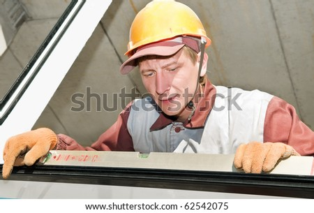 Builder laborer in work wear and hard hat at construction site using level tool - stock photo