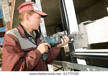 Builder laborer in work wear making a hole with drilling machine - stock photo