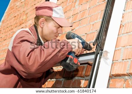 Builder laborer in work wear screwing a screw with screwdriver machine - stock photo