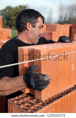 Builder laying bricks - stock photo