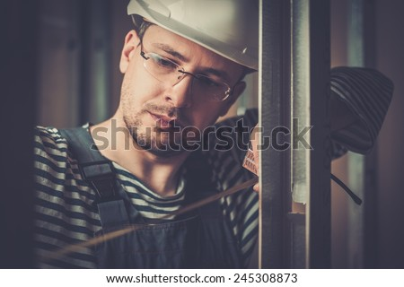 Builder measuring distance with tape during construction  - stock photo