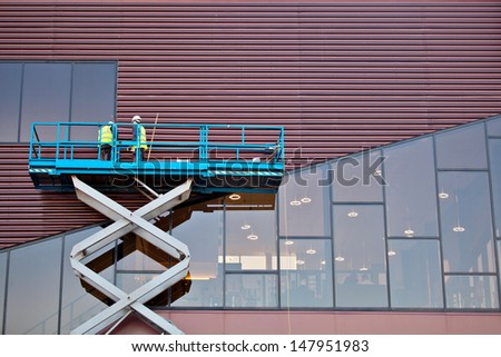 Builder on a Scissor Lift Platform at a construction site. Men at work - stock photo