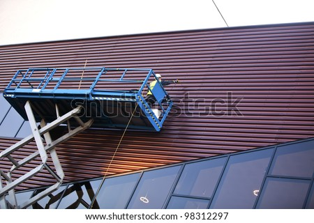 Builder on a Scissor Lift Platform on a construction site. Man at work - stock photo