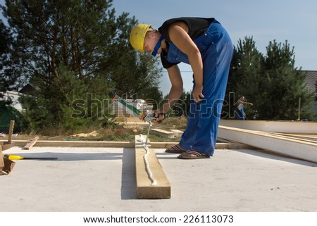 Builder or carpenter applying glue to a wooden beam on a construction site from a glue gun - stock photo