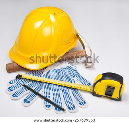 builder's tools - yellow helmet, work gloves, hammer, pen and measure tape over white background - stock photo
