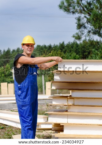 Builder selecting an insulated wooden wall panel from a large stack of supplies on the outdoors building site giving the camera a quizzical serious look - stock photo