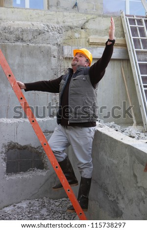 Builder stood by ladder waving - stock photo