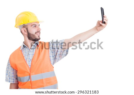 Builder taking a selfie suing smartphone isolated on white background - stock photo