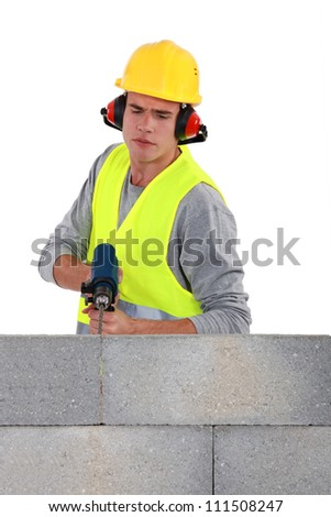 Builder using a masonry drill - stock photo