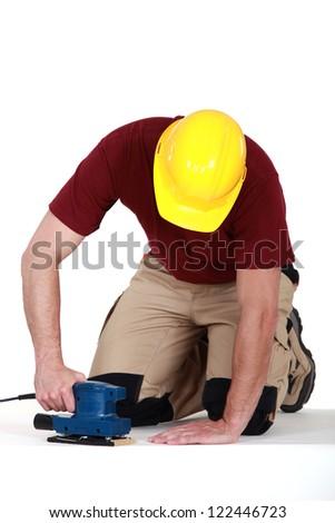 Builder using sander on floor - stock photo