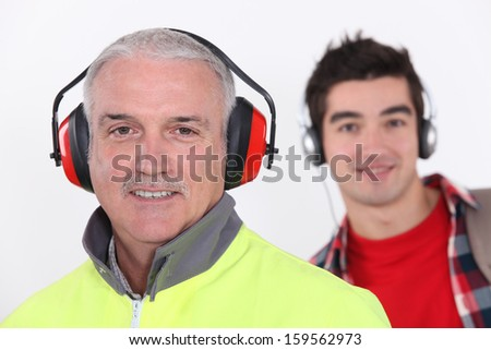 Builder with earmuff stood in front of teenager with headphones - stock photo