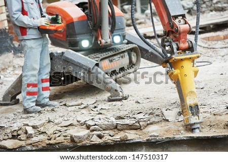 builder worker in safety protective equipment operating construction demolition machine robot - stock photo