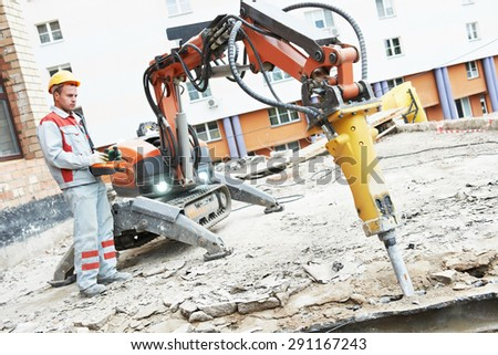 builder worker in safety protective equipment operating construction demolition machine robot. Focus on tool - stock photo