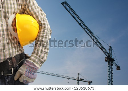 builder worker in uniform and helmet operating with tower crane - stock photo