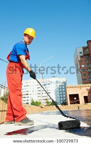 builder worker in uniform covering roof with insulation tar material at construction site - stock photo