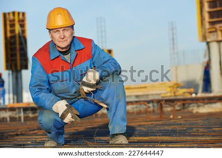 builder worker knitting metal rebar into framework reinforcement for concrete pouring at construction site - stock photo