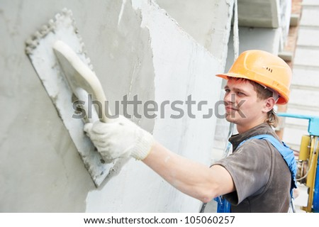 builder worker plastering facade of high-rise building with putty knife - stock photo