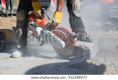 Builder worker with cut-off machine power tool breaking concrete at road construction site - stock photo