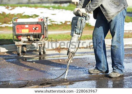 Builder worker with pneumatic hammer drill equipment breaking asphalt at road construction site - stock photo