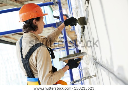 builder worker works with facade joint of building with plaster and spatula - stock photo