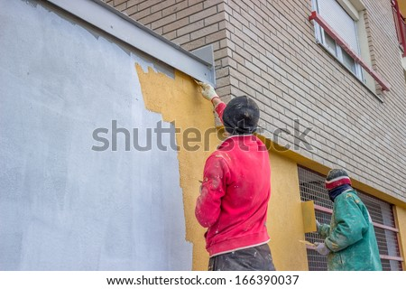 builder workers plastering exterior wall, facade plasterers at work. - stock photo