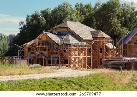 builders cover the roof of a log house - stock photo