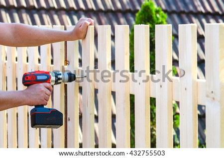 building a wooden fence with a drill and screw. Close up of his hand and the tool in a DIY concept. - stock photo