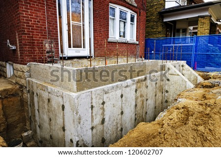 Building addition to residential house with new foundation - stock photo
