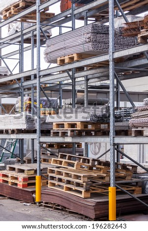 Building and construction materials for sale stored on metal shelves outdoors in a warehouse yard together with wooden pallets for loading, distribution and storage - stock photo