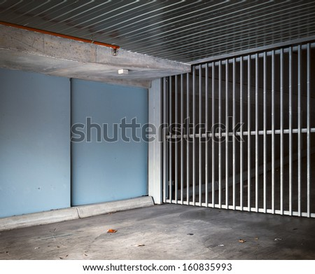 Building and garage entrance ramp and gate. - stock photo