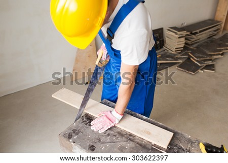 building, carpentry, repair, teamwork and people concept - close up of builder with arm saw sawing board on table - stock photo