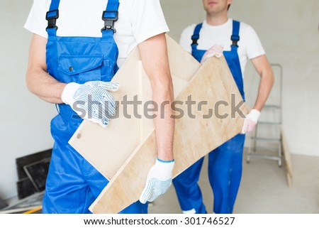 building, carpentry, repair, teamwork and people concept - close up of builders carrying wooden boards - stock photo