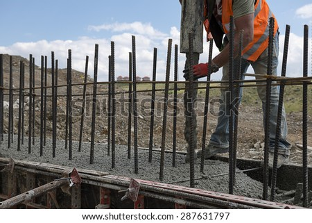 Building construction worker pouring cement or concrete with pump tube. - stock photo