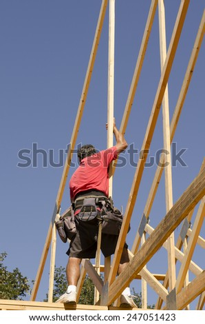 Building contractor carpenter placing new home wood engineered trusses on a residential construction site - stock photo