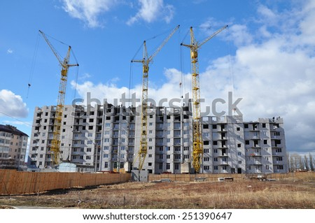 Building cranes and building under construction - stock photo