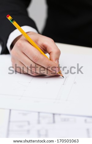 building, developing, consrtuction and architecture concept - male contractor making changes to blueprint - stock photo