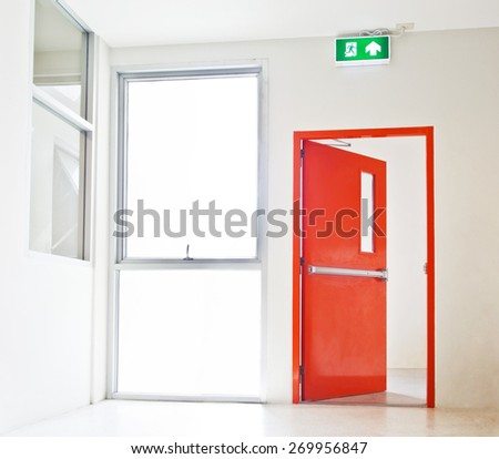 Building Emergency Exit with Exit Sign, red door opening to white - stock photo