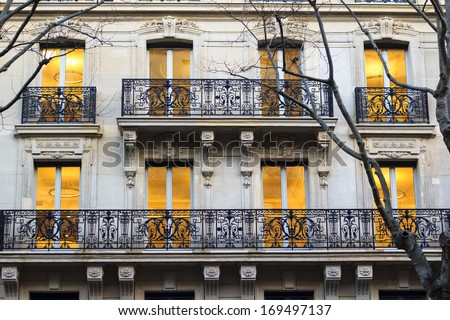 Building facade in Paris - windows just got lit warm yellow in the beginning of the evening. - stock photo