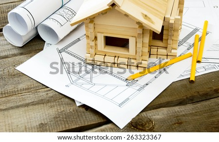 Building house. House construction. Many drawings for building and small wooden house on old wooden background. - stock photo