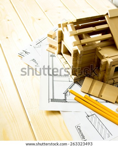 Building house. House construction. Many drawings for building, pencils and small wooden house on wooden background. - stock photo