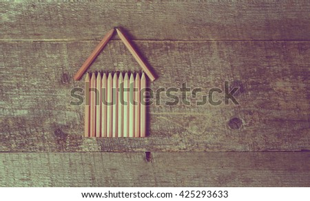 Building house. House construction. small wooden house from pencils on old wooden background. top view. copy space - stock photo