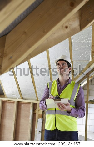 Building Inspector Looking At Roof Of New Property - stock photo