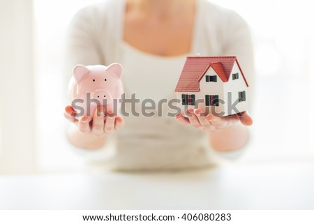 building, mortgage, investment, real estate and property concept - close up of woman holding home or house model and piggy bank - stock photo