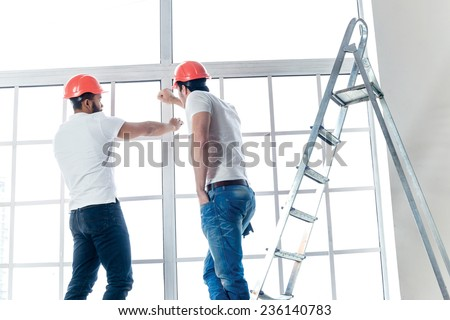 Building, moving and repairs in the apartment. Two workers make measurements of windows and repairs in a new apartment while ladder stands in an empty apartment. - stock photo